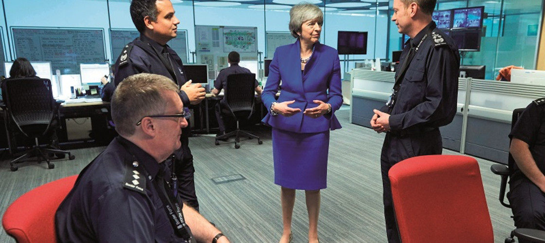 Theresa May speaks to UK Border Force officers during a visit to Heathrow