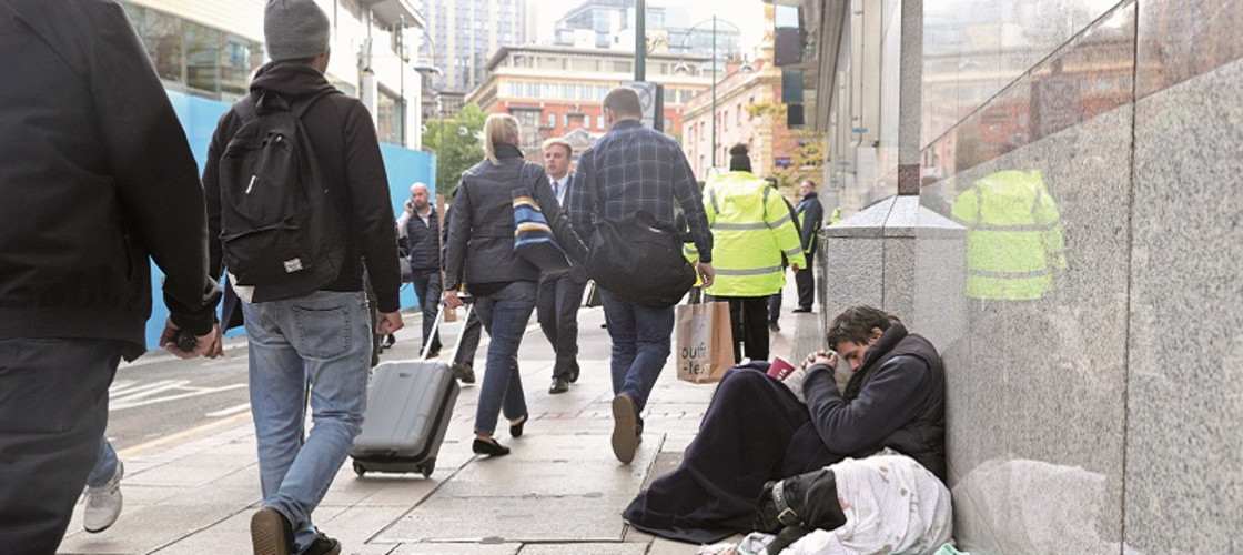 A homeless man on the street outside the Conservative Party conference in Birmingham last year