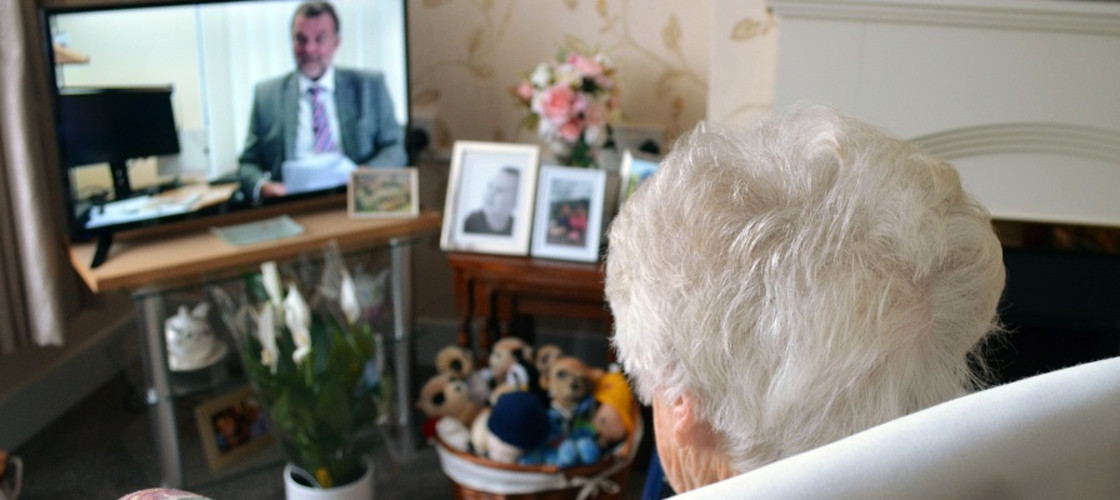 An elderly woman watching TV