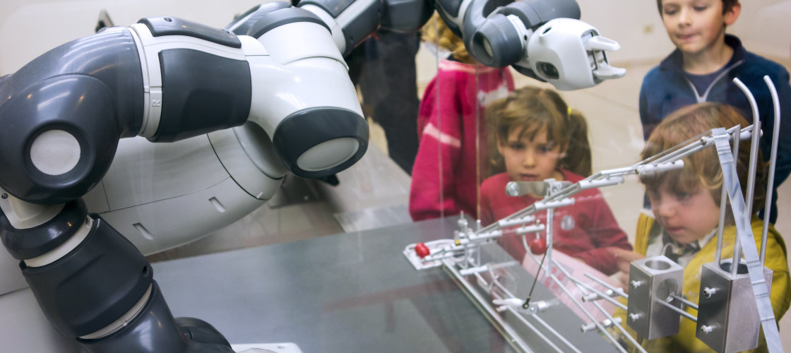 Children looking at demonstration with industrial robot arms