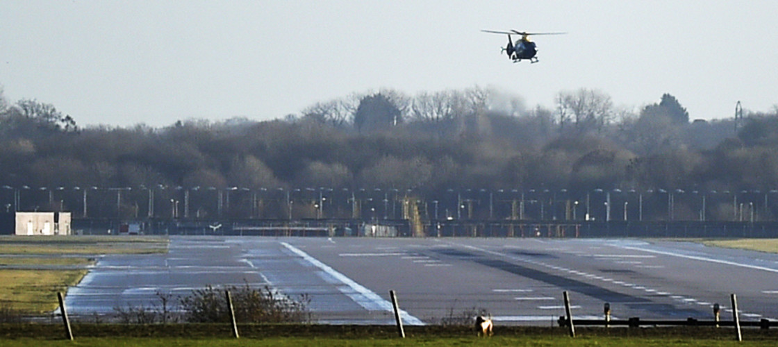 A police helicopter flies over the runway at Gatwick airport after drones were spotted