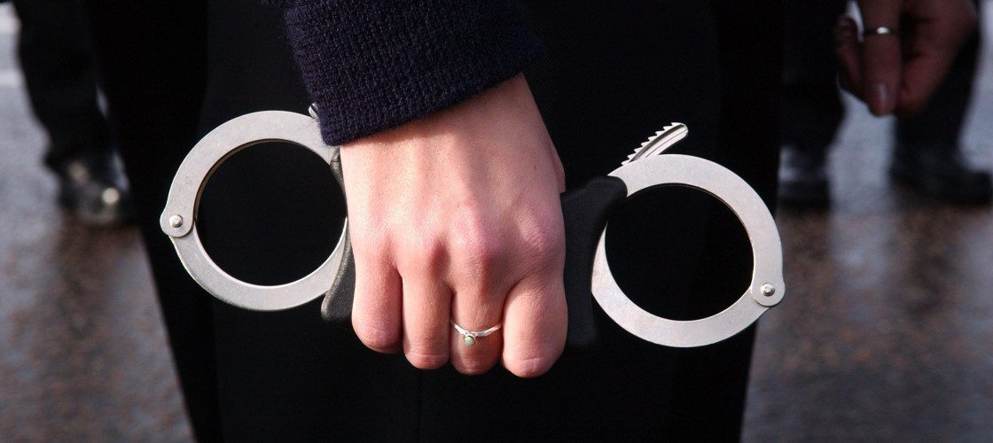 A person holds a pair of handcuffs