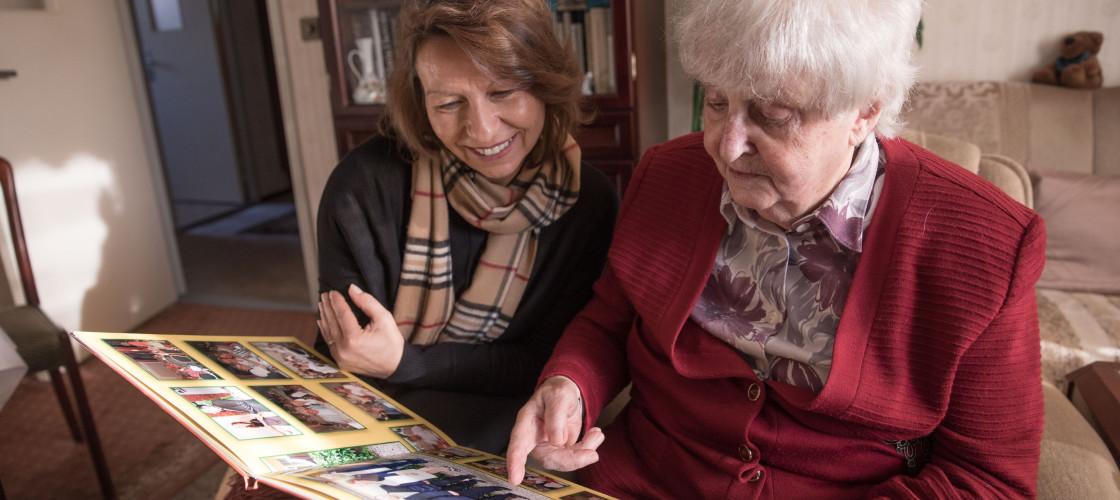 An elderly woman sits an looks through a photo album with a friend