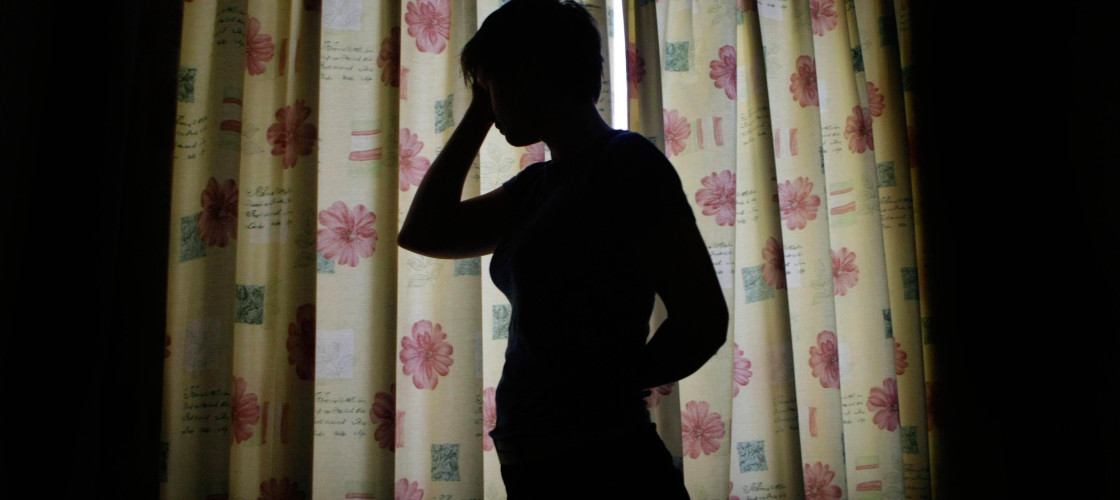 A silhouette of a child standing in front of a window