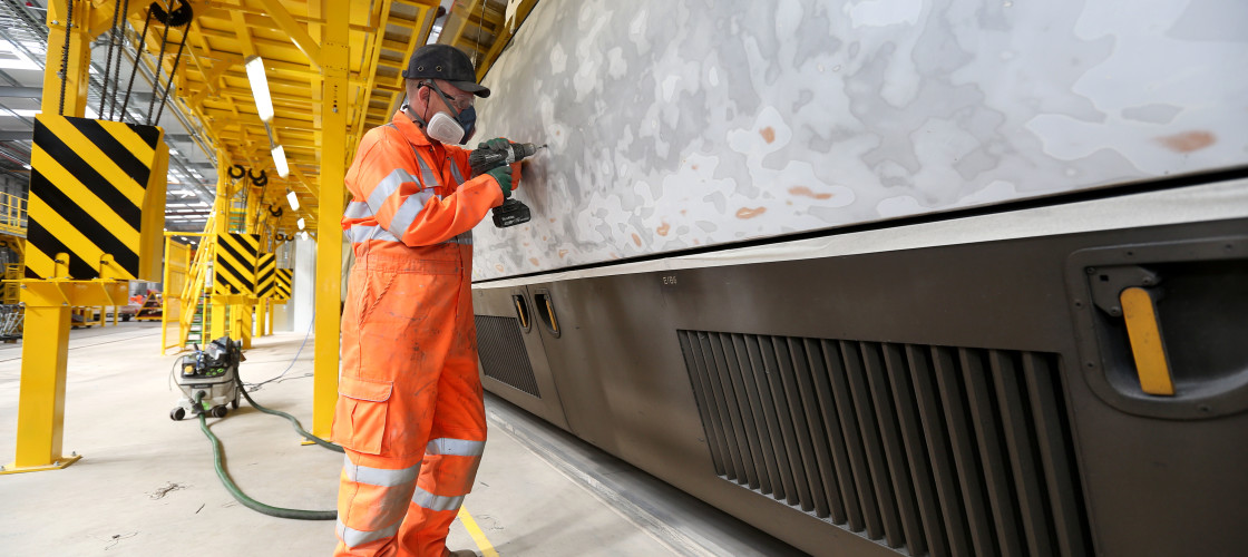 A man in a boiler suit and PPE equipment drills a hole in a train