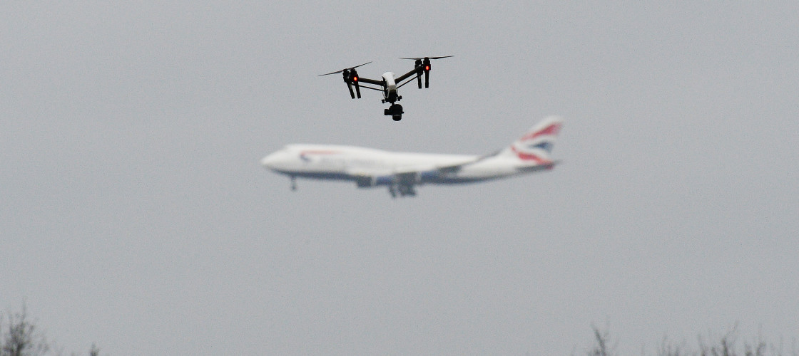 A drone flies in Hanworth Park in west London, as a British Airways 747 plane prepares to land at Heathrow Airport behind.