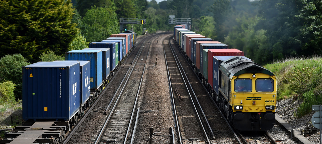 two rail freight trains pass on the tracks as they make their way through Worting Junction near to Basingstoke, Hampshire.