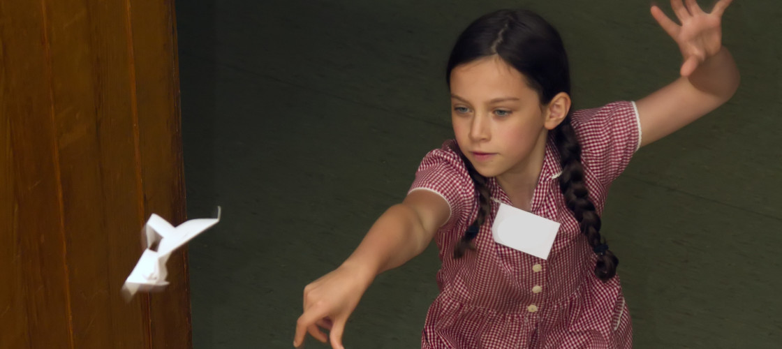 A young girl throws a paper aeroplane