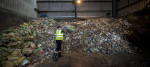 A worker at a waste management site throws waste into a pile