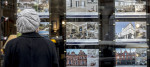 A woman looks at properties advertised in an estate agents window