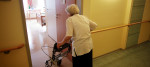 An elderly woman walks into her care home room