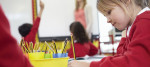 Pupils Sitting At Table As Teacher Stands By Whiteboard