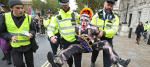 Police hold a protester during an Extinction Rebellion (XR) demonstration in Westminster, London.