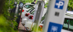 Electric cars stand next to charging stations