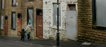 A woman and child make their way past a boarded up houses on a street in Accrington in Lancashire.