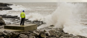 Construction worker looks out to see as waves crash in