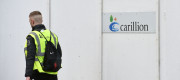 A workman walks past a Carillion sign