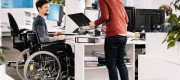 A man is sitting in a wheelchair working in an office.