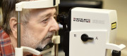Man rests chin on diagnostic eye test kit