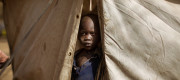 A young child looks out from a tent in South Sudan
