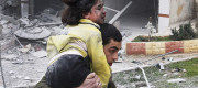 Syrian man carries his sister who was wounded in a government airstrike hit the neighborhood of Ansari, in Aleppo, Syria