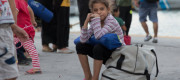 A young refugee girl waits, after disembarking the Eleftherios Venizelos ferry