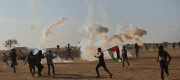 Palestinian protesters take part during clashes with Israeli soldiers at the border fence with Israel east of Khan Yunis in the southern Gaza Strip on 15th May 2018