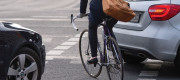 A cyclist passes between cars