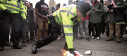 A police officer extinguishes a flag set alight outside Parliament by protesters