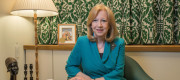 Eleanor Laing MP sits in front of curtains patterned with green portcullises in her House of Commons office