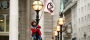 A young protester standing on a lamp post, in front of The Royal Exchange, London, during an Extinction Rebellion (XR) climate change protest.