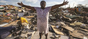 Aliana Alexis of Haiti stands on what is left of her home after destruction from Hurricane Dorian (Sep 2019)