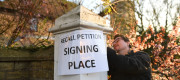 A 'recall petition signing place' sign is placed outside Bedford Hall in Thorney, Peterborough