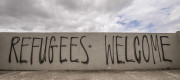Graffiti on a wall reading 'Refugees Welcome'