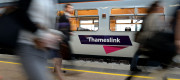 Commuters passing a Thameslink train operated by Govia Thameslink Railway (GTR)