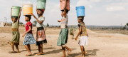 Girls carry water away from a privately owned shallow well