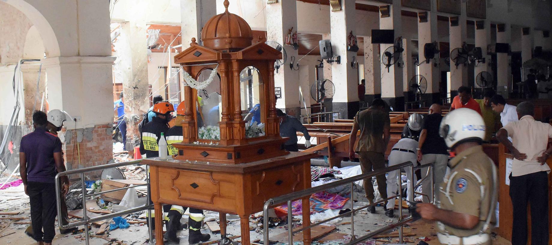 People work at a blast scene at St. Anthony's Church in Kochchikade in Colombo, Sri Lanka