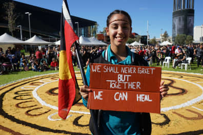 Girl holding Aboriginal flag and smiling