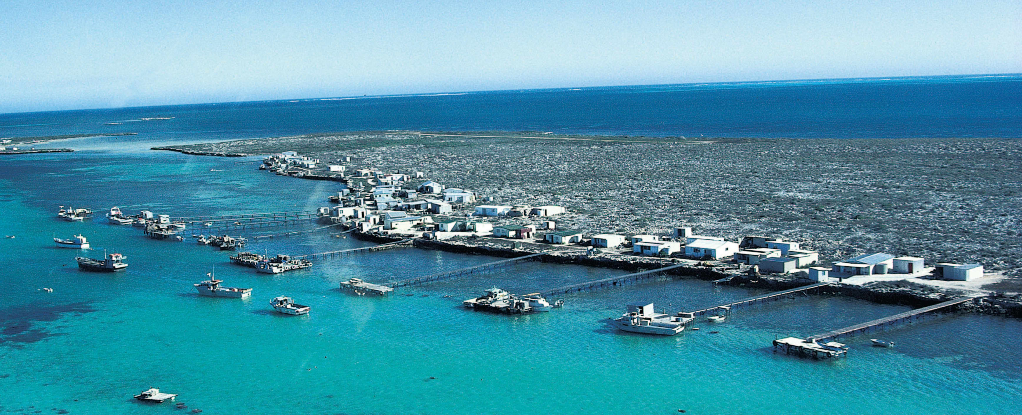 Aerial view of fishing shacks with bright blue water and visible reef