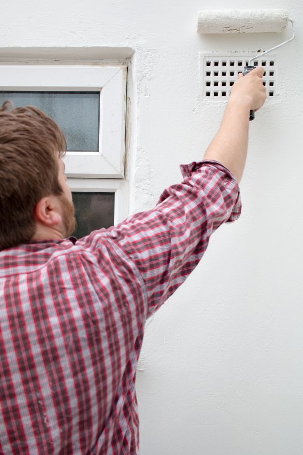 Stock photo of man painting on a wall