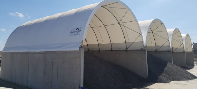 Concrete wall mounted DomeShelters to store sand and gravel.