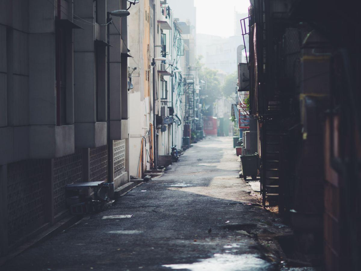 Photograph of empty walkway alleyway between building during the day