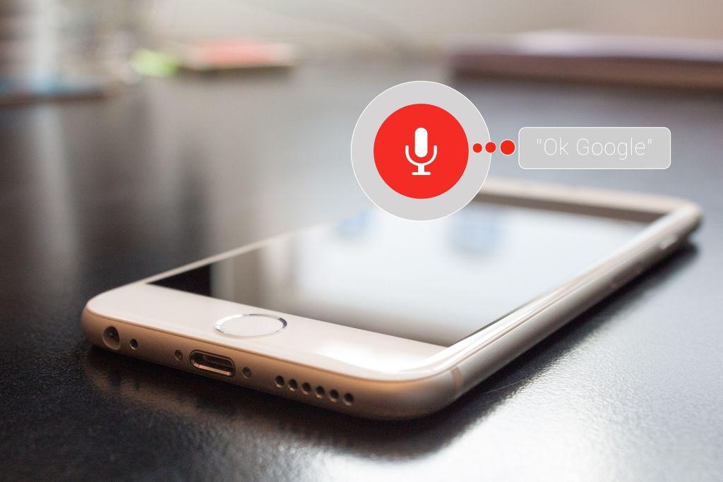 Ein Smartphone mit einer Sprechblase und einem Aufnahmegerät als Zeichen drin. Ok Google steht in der Sprechblase geschrieben.