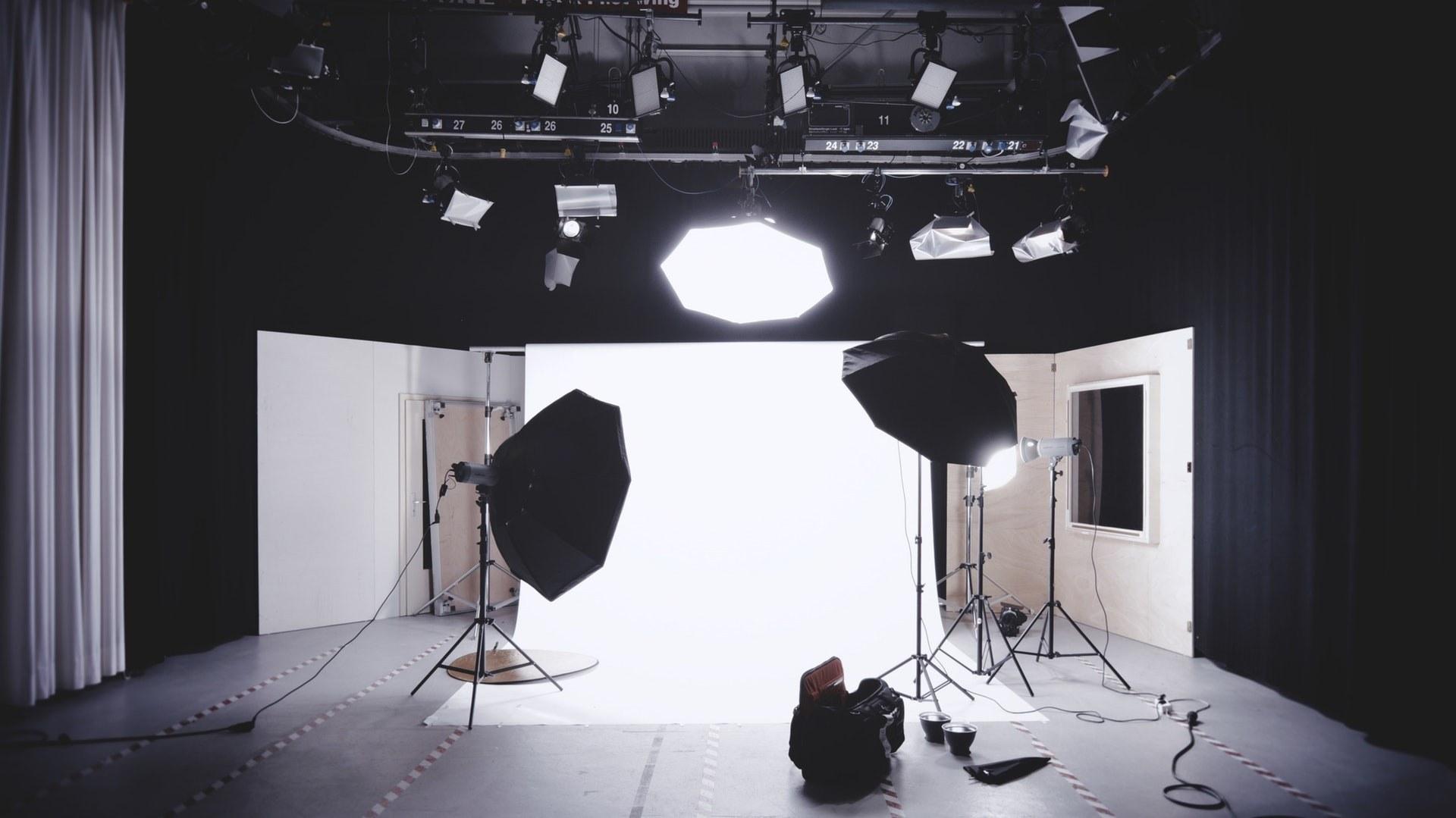 Ein schwarz weißes Bild, welches ein Fotoshooting darstellt. Große Softboxen und Kameraequipment ist aufgebaut. Im Hintergrund ist eine weiße Leinwand.