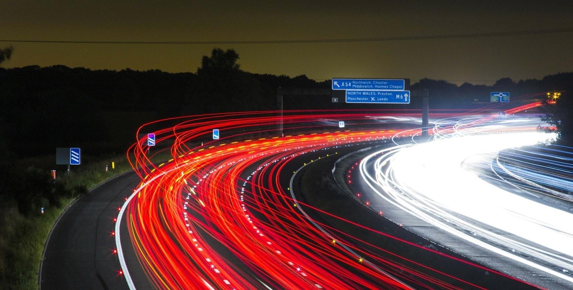 Eine Autobahn bei Nacht. Blaue Verkehrsschilder und rote und helle Lichteffekte auf der Fahrbahn. Die Fahrbahn steht für den Weg des Ranking-Algorithmus.
