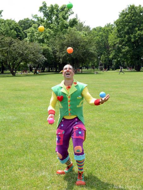 Zsonglőr bohóc 5 színes labdával zsonglőrködik