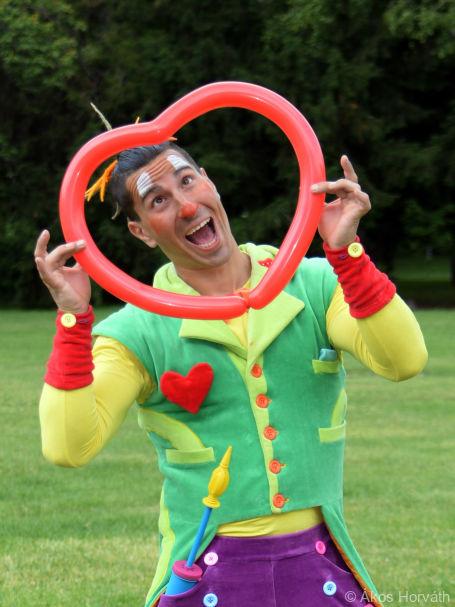 Lufihajtogató bohóc piros szívecskét készít lufiból