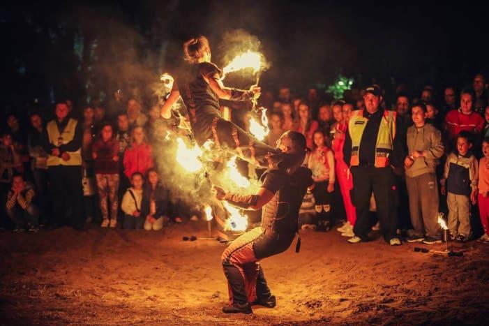 Tűzzsonglőr előadás a közönség gyűrűjében