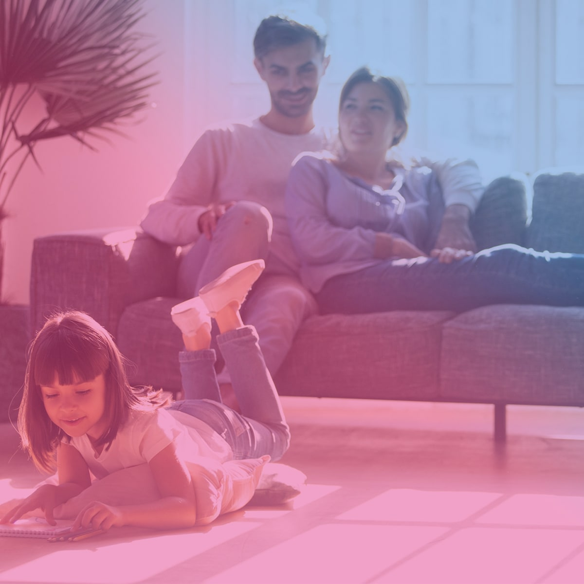 Parents on a couch with female child playing on the floor