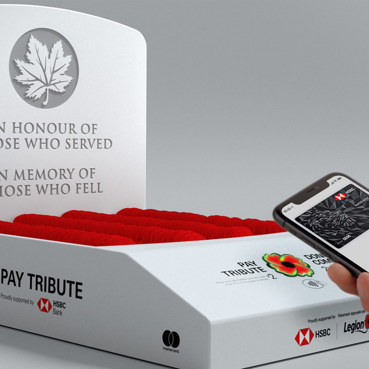 "White background, Pay Tribute box containing poppies. Hand in front holding cellphone with the HSBC RCL Pay Tribute App. Words on the box ""In honour of those who served. In memory of those who fell."